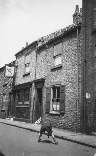 Black and white photo of terraced street, mid 1950s