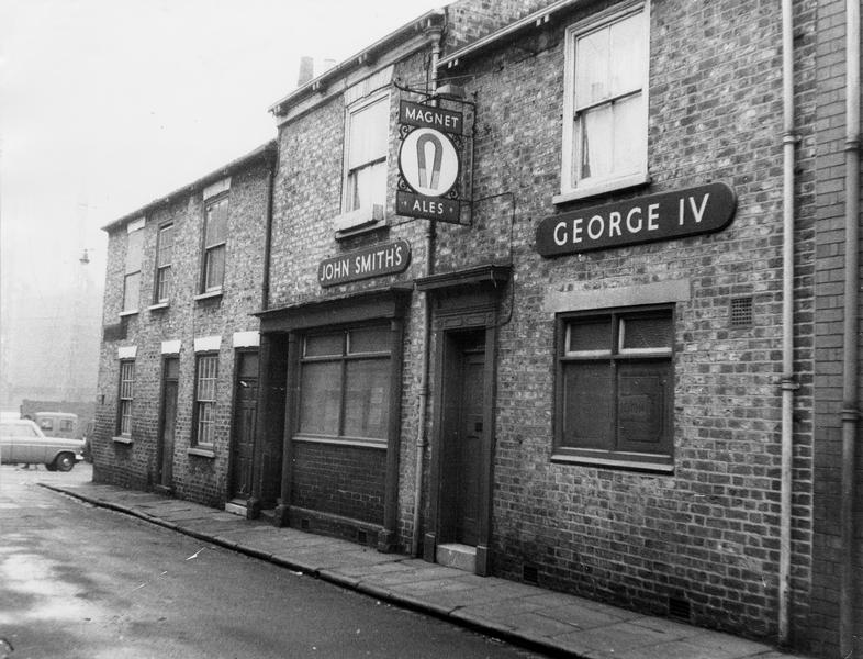Black and white photo of street of terraced houses and pub