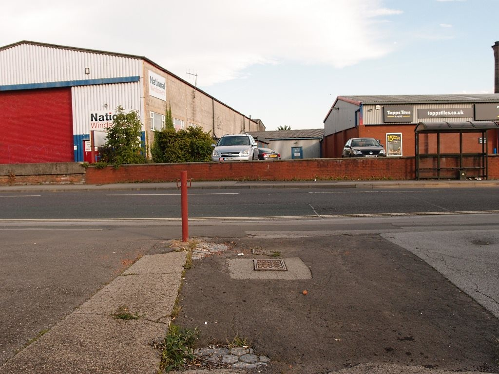 Modern industrial units, foreground tarmac paving with older Victorian paviours showing underneath